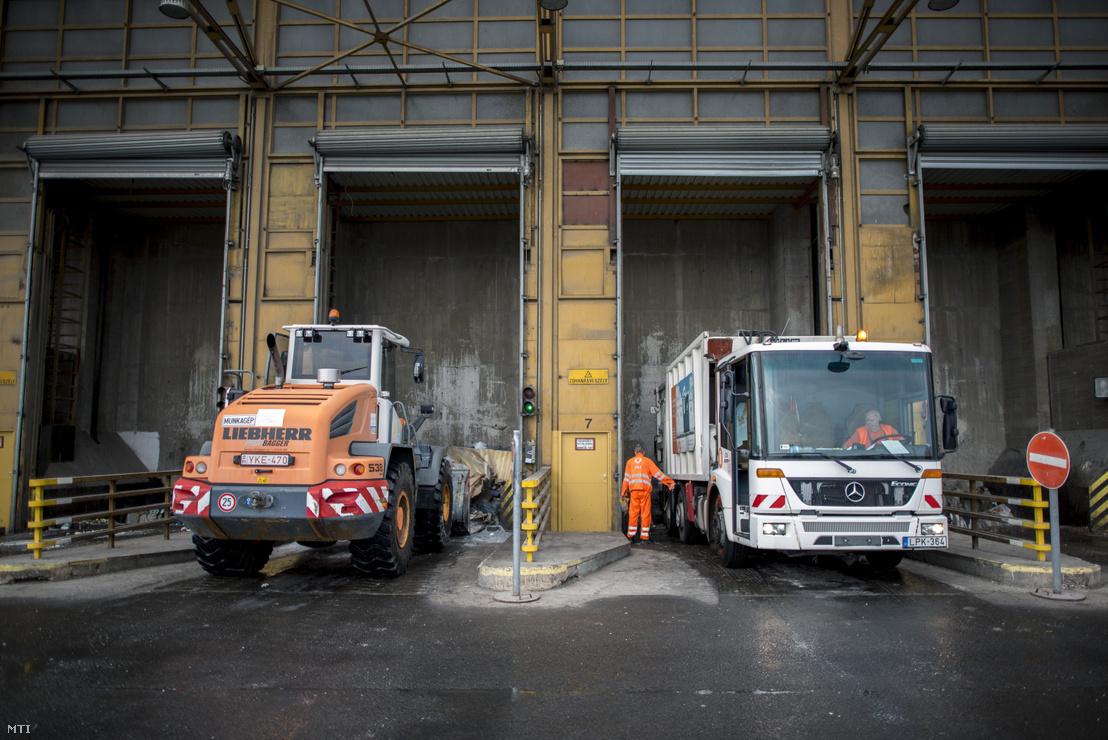 Homlokrakodó és egy kukásautó a hulladékbunkerbe üríti a hulladékot Rákospalotán a Fővárosi Hulladékhasznosító Műben 2018. július 23-án.