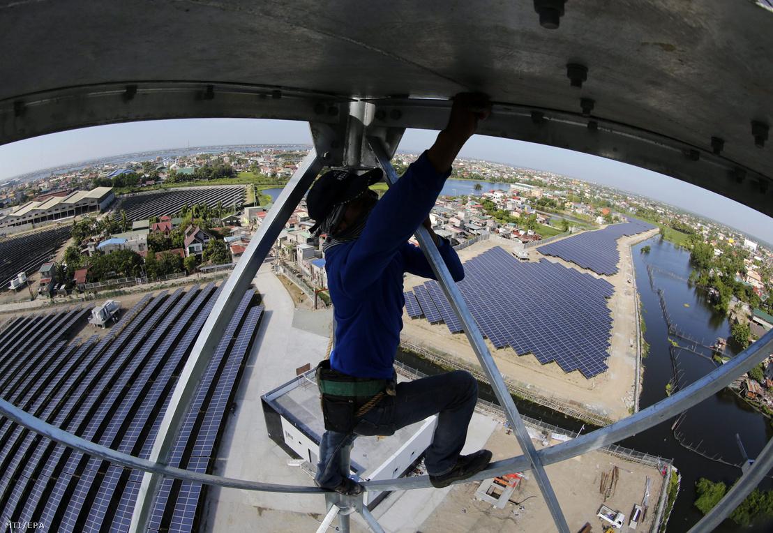 Egy Fülöp-szigeteki munkás egy naperőmű tornyát építi a fővárostól Manilától északra fekvő Valenzuelában 2015. november 30-án. A tizenegy hektáron elterülő 32.692 napelemből álló napelemfarm naponta 86 megawatt energiát termel.
