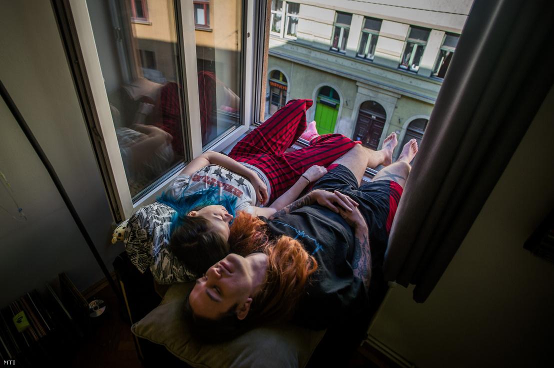 A koronavírus-járvány miatt önkéntes karanténban pár pihen budapesti otthonuk ablakában 2020. április 6-án