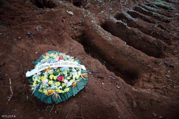 Koszorú egy sírhanton a frissen ásott sírok mellett a São Pauló-i Vila Formosa temetőben 2020. május 18-án