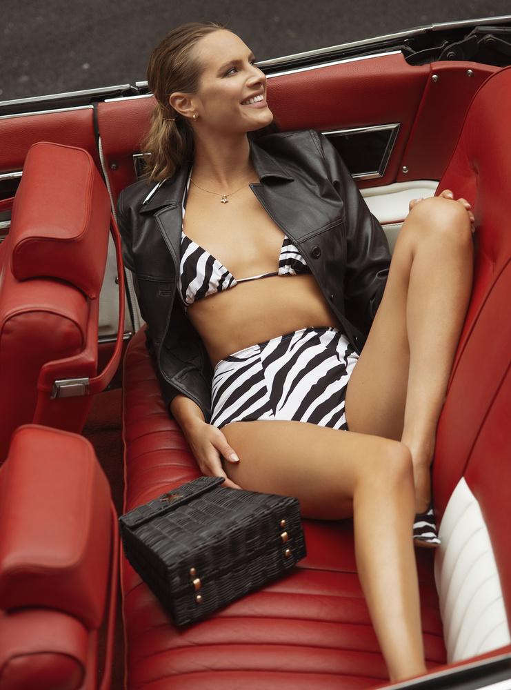 A képen egy 60-as éveket idéző bikiniben és bőrkabátban lazul, persze nem maradhat el a kiegészítő sem