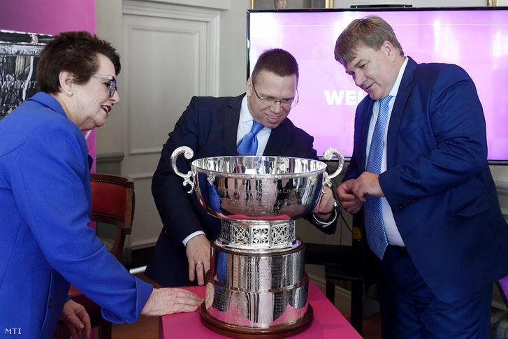 Fürjes Balázs nemzetközi sportpályázatokért felelős kormánybiztos (középen), Szűcs Lajos, a Magyar Tenisz Szövetség (MTSZ) elnöke, országgyűlési képviselő (jobbra) és Billie Jean King legendás amerikai teniszező, a londoni Queen's Tennis Clubban tartott sajtótájékoztatón 2019. június 27-én. Az eseményen bejelentették, hogy Magyarország rendezi meg az átszervezés alatt álló női tenisz Fed Kupa döntőjét 2020-ban, 2021-ben és 2022-ben.