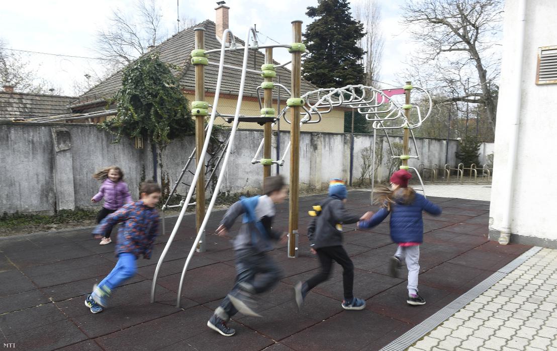 Gyerekek játszanak a Kőbányai Kertvárosi Általános Iskola udvarán 2020. március 31-én. Az intézmény kislétszámú gyermekfelügyeletet biztosít azoknak a tanulóknak akiknek az otthon tartózkodása nem megoldható a koronavírus-járvány terjedésének megfékezése érdekében bevezetett digitális tanrend ideje alatt.