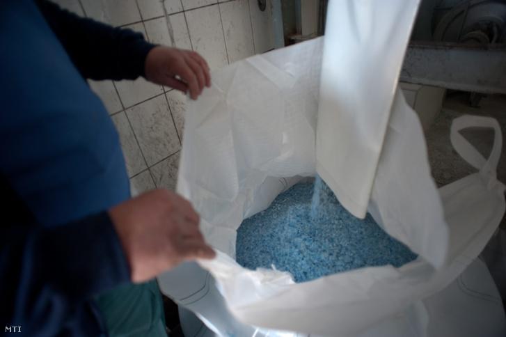 PET-palackokból készült átmosott műanyag darát zsákolnak egy X. kerületi szelektív hulladékfeldolgozó telepen.