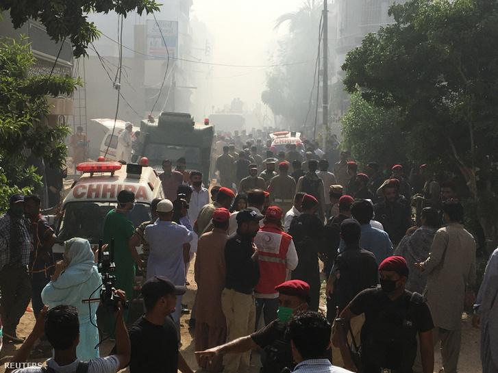 Mentősök érkeznek a helyszínre, ahol lezuhant egy utasszállító repülőgép Karacsiban 2020. május 22-én