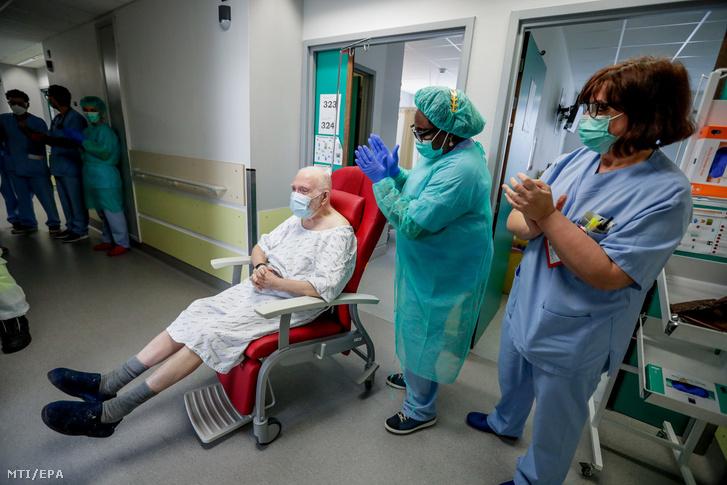 A koronavírus okozta betegségből meggyógyult és haza készülő 85 éves Andrét megtapsolják kórházi dolgozók a brüsszeli Etterbeek-Ixelles Kórházban 2020. április 29-én.