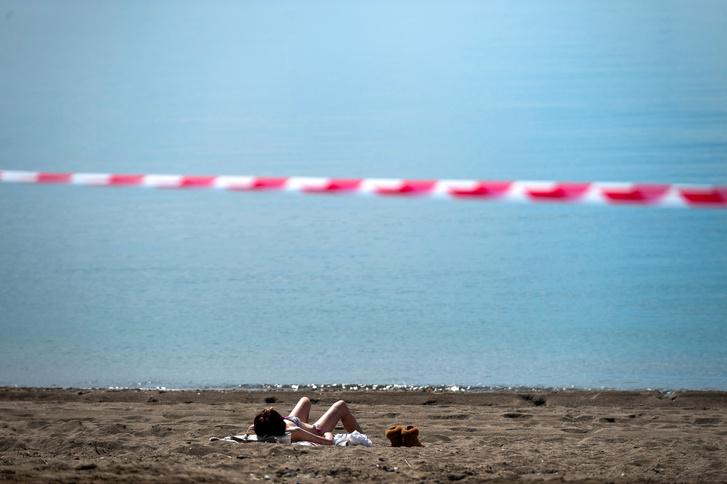 Málagai nő napozik a tengerparton május 20-án, a korlátozások részleges feloldásának kezdetén