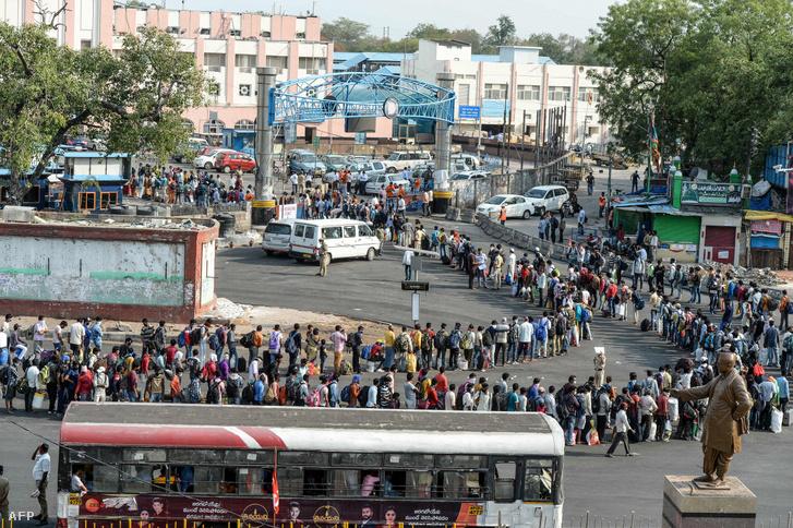 A különvonatokhoz sorban álló indiai munkások és családtagjaik