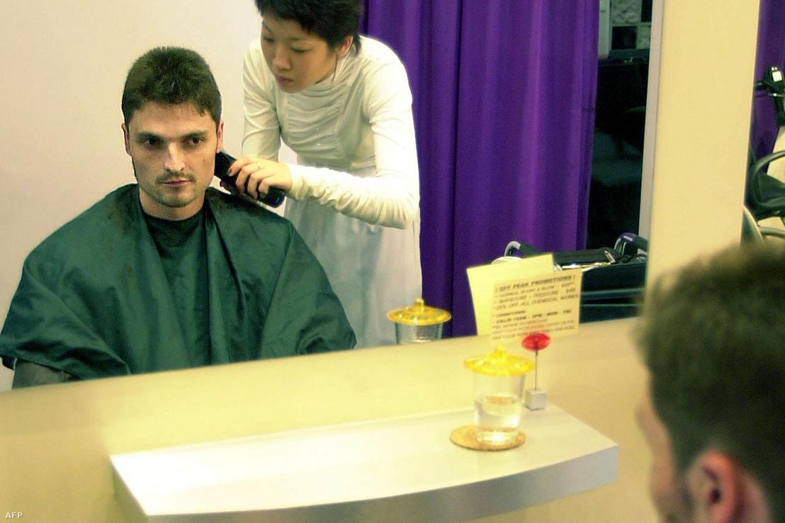 Lutz Pfannenstielt hajvágás közben a Raffles hotel szalonjában, miután kiengedték a szingapúri börtönből 2001. április 17-én