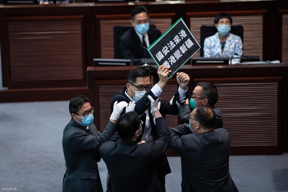A biztonsági őrök kivezetik Lam Csök-tim ellenzéki képviselőt a hongkongi parlament ülésterméből, ahol dulakodás tört ki a Peking-párti és a demokráciapárti képviselők között a kínai nemzetbiztonsági törvénytervezet miatt 2020. május 22-én.