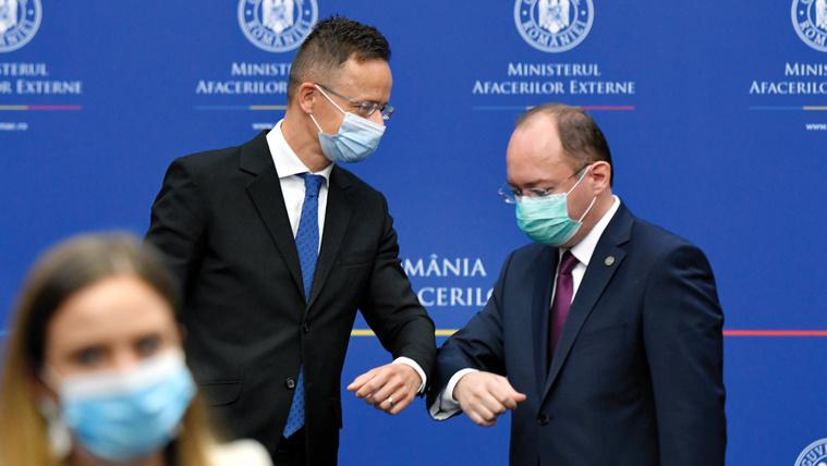 Szijjártó Péter külgazdasági és külügyminiszter (b) és Bogdan Aurescu román külügyminiszter könyökérintéssel üdvözli egymást bukaresti sajtótájékoztatójukon 2020. május 26-án.