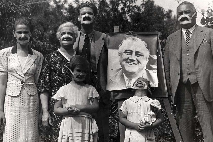 Emberek furcsa szerkezettel az arcukon Roosevelt képe előtt.