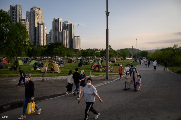 Arcmaszkos emberek sétálnak egy szöuli parkban 2020. május 24-én