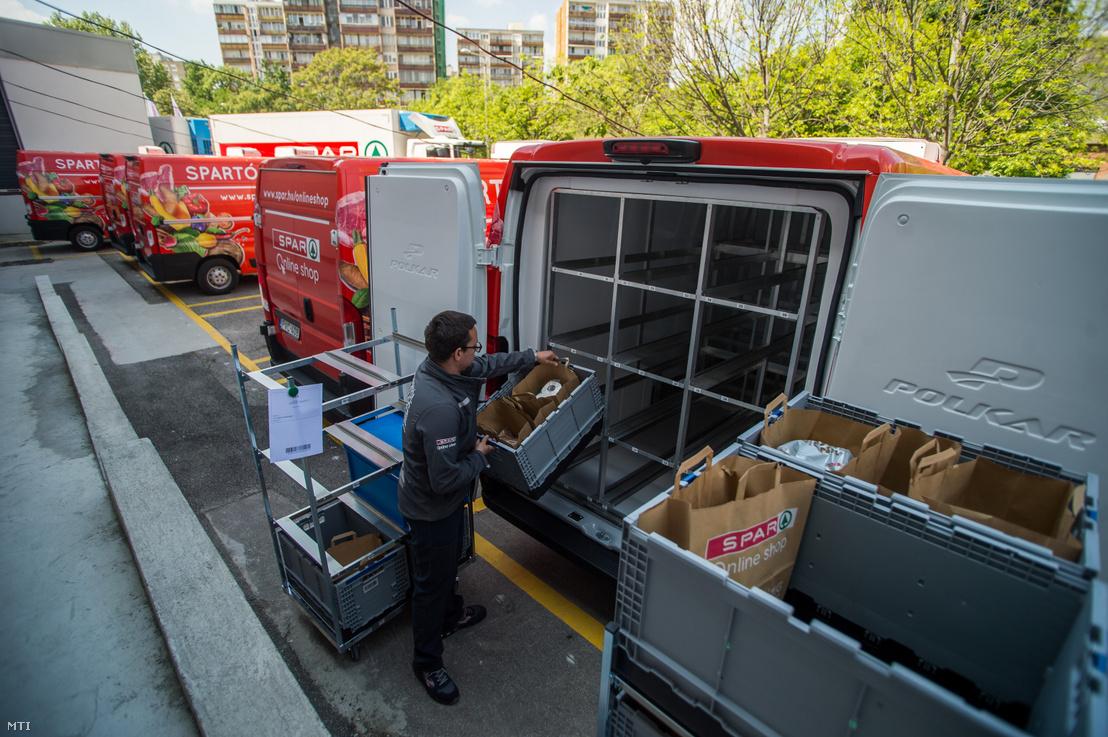 Egy dolgozó a megrendelt árukat pakolja a kisteherautóba a webshop háttérterületén a XX. kerületi Pesterzsébeti Interspar hipermarketnél 2019. május 8-án.