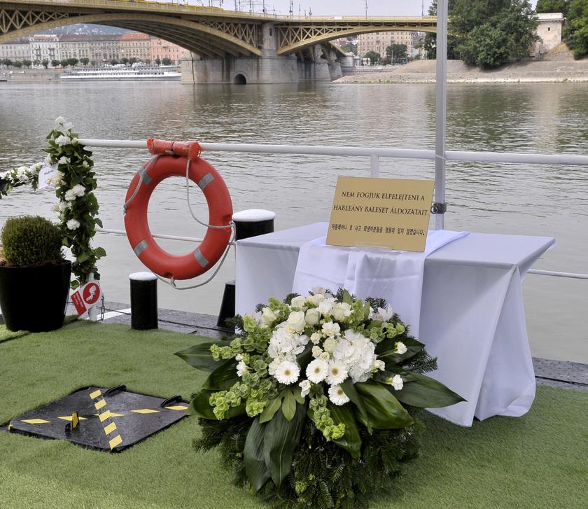 Koszorú az áldozatoknak emléket állító plakett előtt.