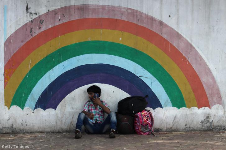 Utazó munkás pihen meg egy graffiti mellett Mumbaiban
