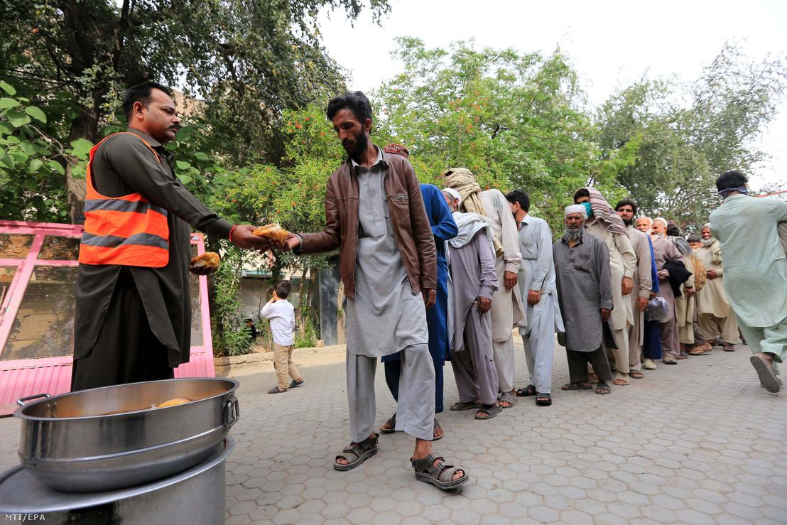 Ételt osztanak a rászorulóknak a pakisztáni Pesavarban 2020. április 14-én a koronavírus-járvány idején