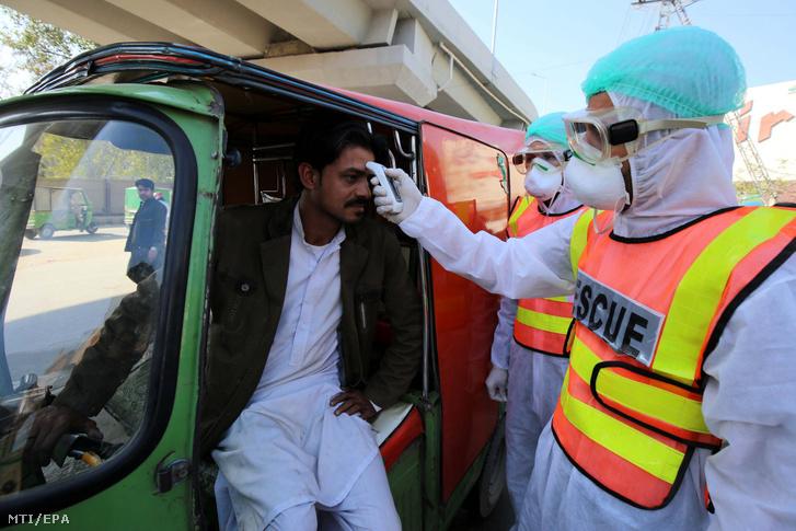 Védőruhát viselő pakisztáni egészségügyi alkalmazottak egy férfi testhőmérsékletét mérik Pesavarban