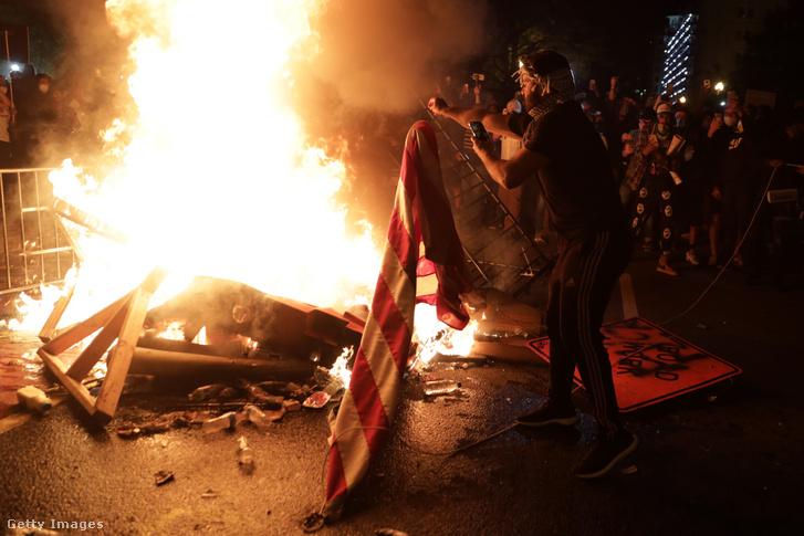 Amerikai zászlót dob a tűzre egy tüntető a Fehár Ház közelében zajló tüntetésen 2020. május 31-én