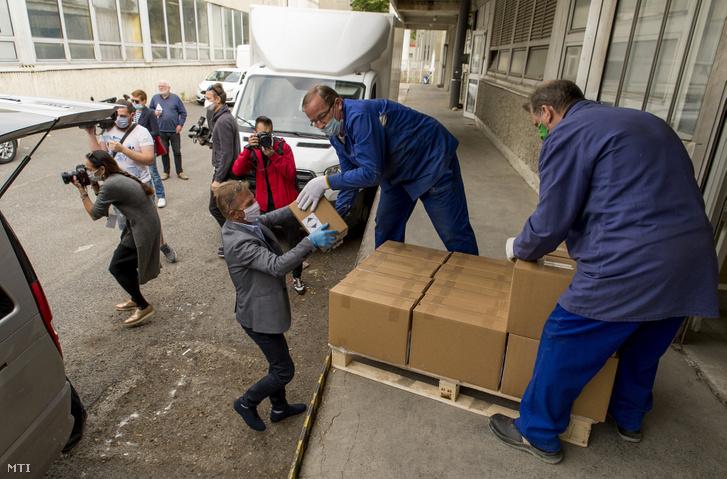 A Graboplast Zrt. saját fejlesztésű fertőtlenítőszerét pakolják ki egy kisteherautóból a győri Petz Aladár Megyei Oktató Kórház udvarán a koronavírus-járvány idején 2020. április 29-én