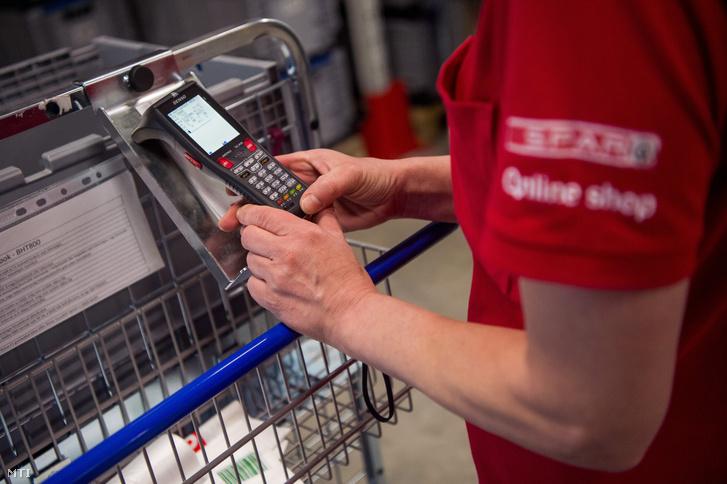Egy dolgozó rendeléseket ellenőriz a webshop háttérterületén a XX. kerületi Pesterzsébeti Interspar hipermarketben 2019. május 8-án