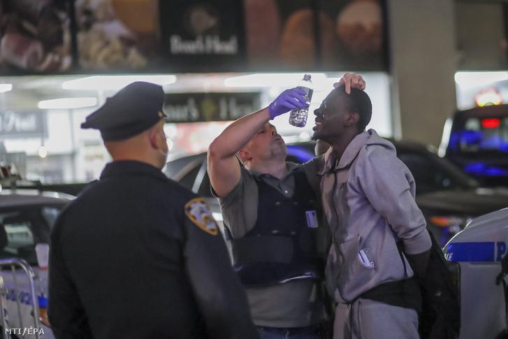 Őrizetbe vett fosztogató sebét ápolják rendőrök a New York-i Manhattanben június 1.-én