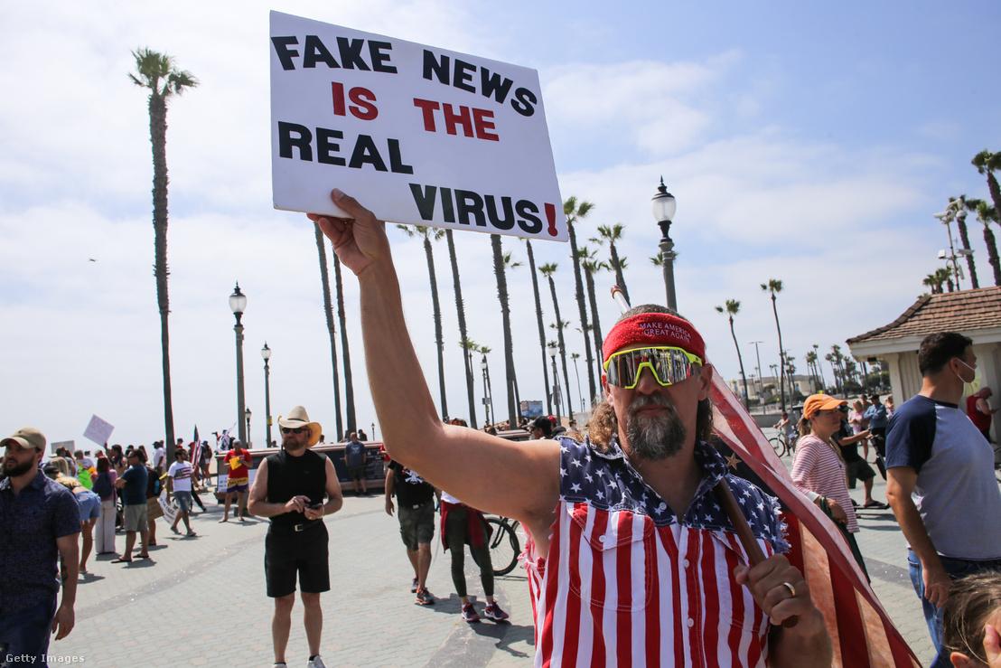 """""""Az álhír a valódi vírus"""" – áll egy a kaliforniai Huntington Beachen, a gazdaság újraindításáért tüntető férfi tábláján 2020. május 9-én"""