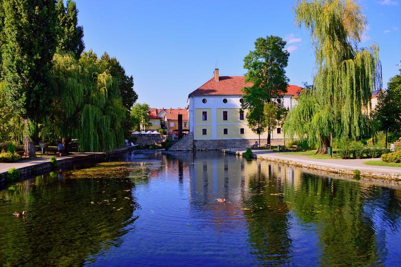 A hangulatos város főterén egy tó vonzza a kirándulókat. Melyik települést ábrázolja a kép?