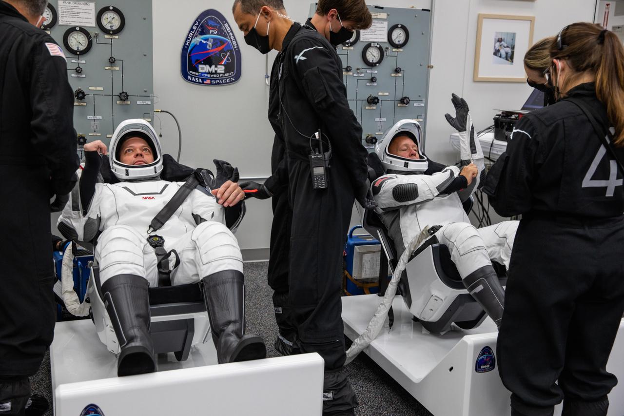 Május 30-án, magyar idő szerint 13:43-kor az űrhajósok már beöltözve várták, hogy elindulhassanak a startálás felé. A fotó a Neil A. Armstrong-ról elnevezett előkészítő épület öltözőjében készült, ugyanabban a helyiségben, ahol a holdraszállás űrhajósai is magukra öltötték szkafandereiket.