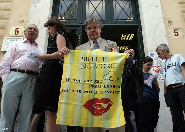 """A görög-amerikai Paul Thymou leszboszi lakos """"Ha nem leszboszi vagy, nem vagy leszbikus"""" feliratú táblát tart egy athéni bírósági épület előtt 2008. június 10-én. Tőle balra látható Dimitrisz Lambru, aki a bíróság elé vitte a perre menő leszbosziak ügyét."""
