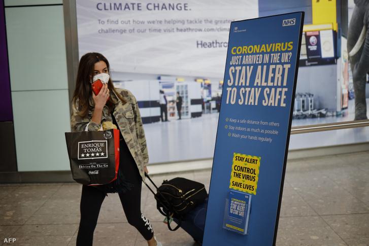 A londoni Heathrow repülőtérre érkező utast tájékoztatja egy molinó a koronavírusról 2020. május 22-én