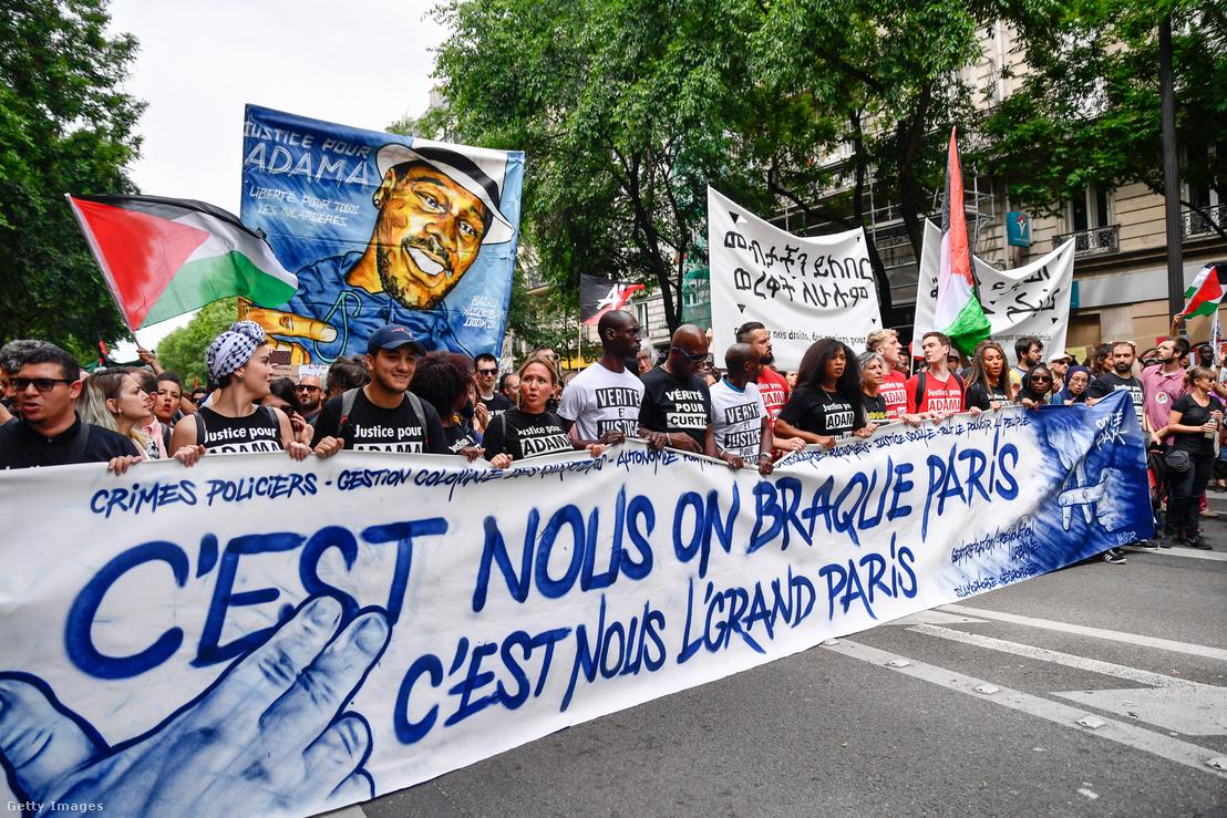 Adama Traorét ábrázoló molinóval tüntetők vonulnak Párizsban 2020. május 26-án
