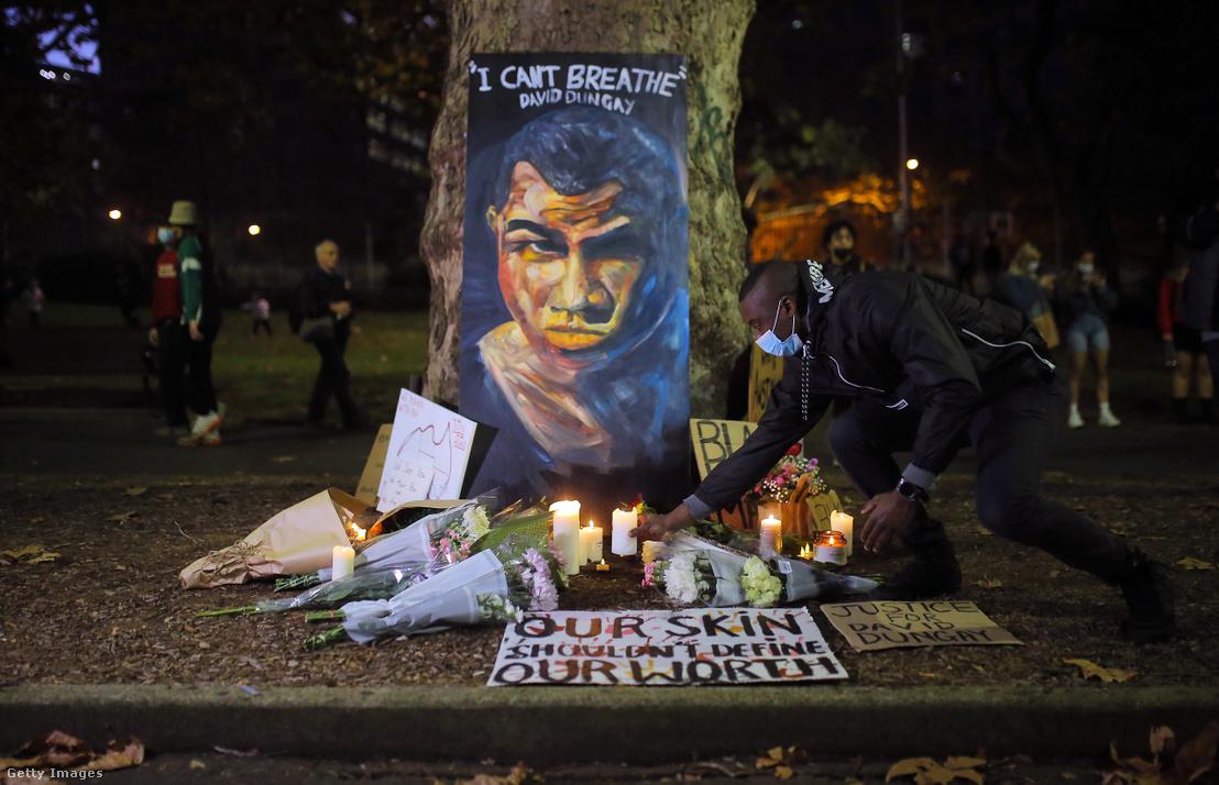 David Dungay-t ábrázoló kép és az őslakos férfi halálának emléket állító gyertyagyújtás a Sydney-ben zajló tüntetésen 2020. június 6-án.