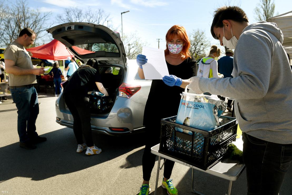Segítők ellenőrzik és pakolják az interneten leadott rendeléseket a dunakeszi drive-in termelői piacon 2020. április 10-én.