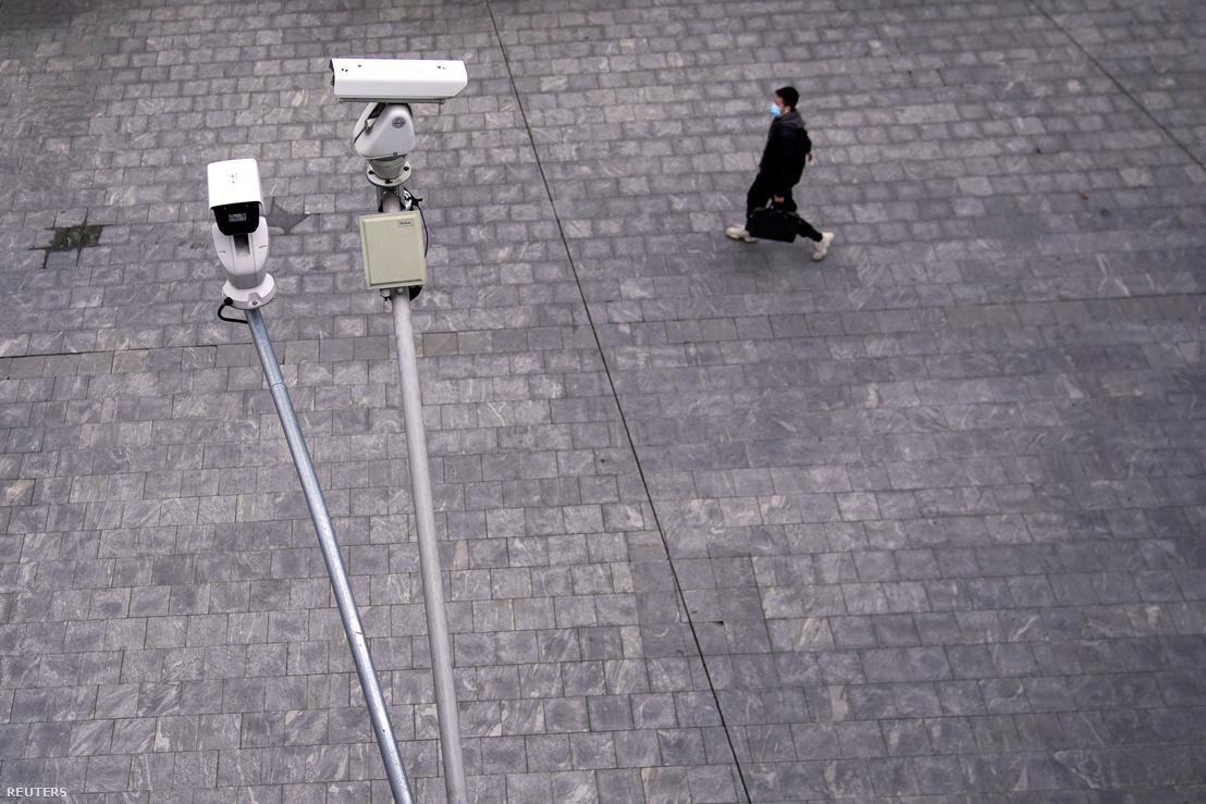 Biztonsági kamera alatt sétál el egy járókelő Shanghaiban koronavírus-járvány idején 2020. február 28-án