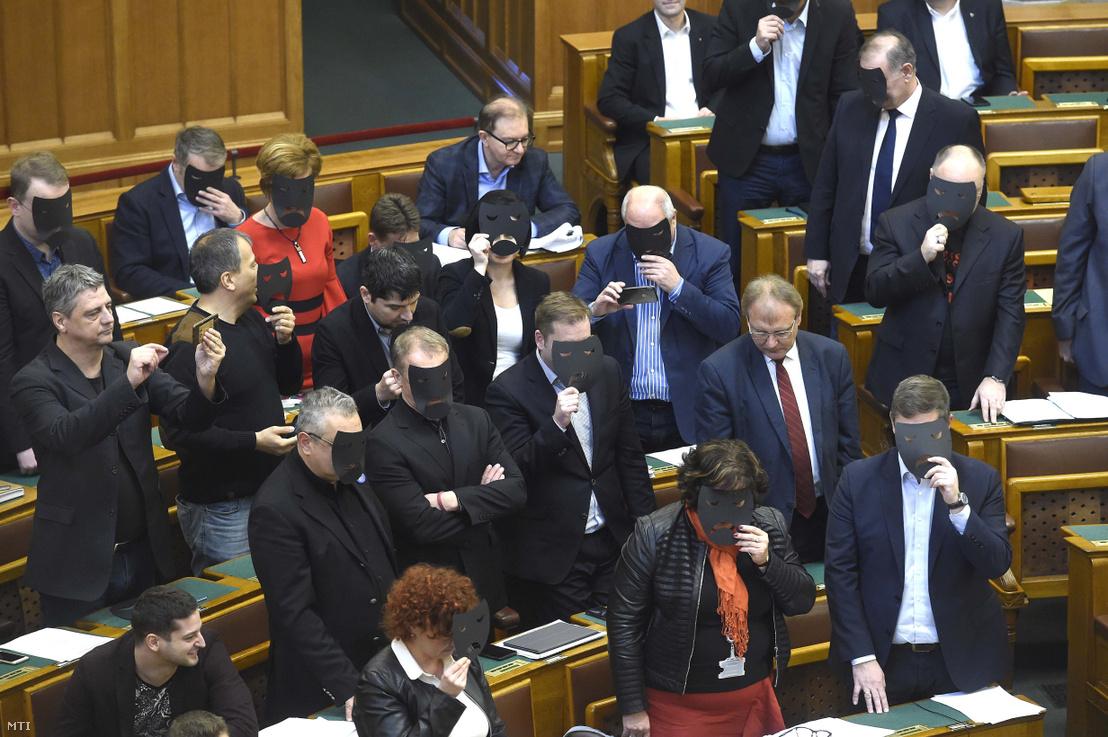 A DK és az MSZP képviselői a kulturális törvénycsomag szavazása közben tiltakozásul felállnak és fekete maszkot tartanak az arcuk elé az Országgyűlés plenáris ülésén 2019. december 11-én. A kormánypárt kommunikációja szerint a törvénymódosítást a Katona József Színház zaklatási ügye tette indokolttá.