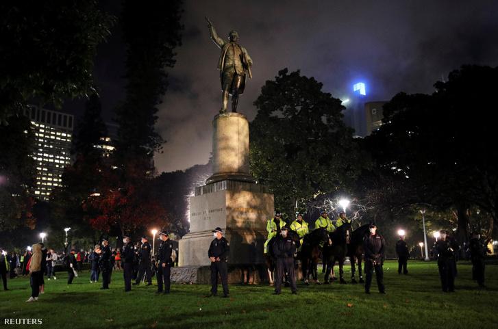 Rendőrök védik a sydney-i Cook-szobrot június 12-én