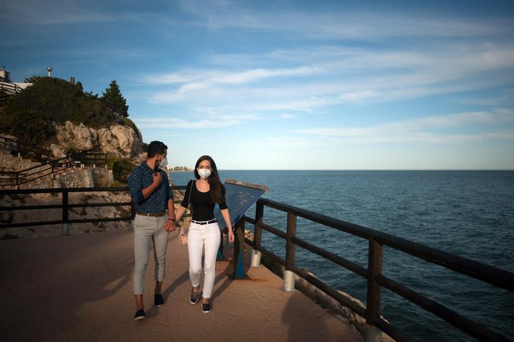 Arcmaszkot viselő belföldi turisták a málagai El Cantal sziklánál 2020. június 13-án. A korlátozások enyhítésének harmadik szakaszában az ország lakói már utazhatnak a saját autonóm közösségükön belül