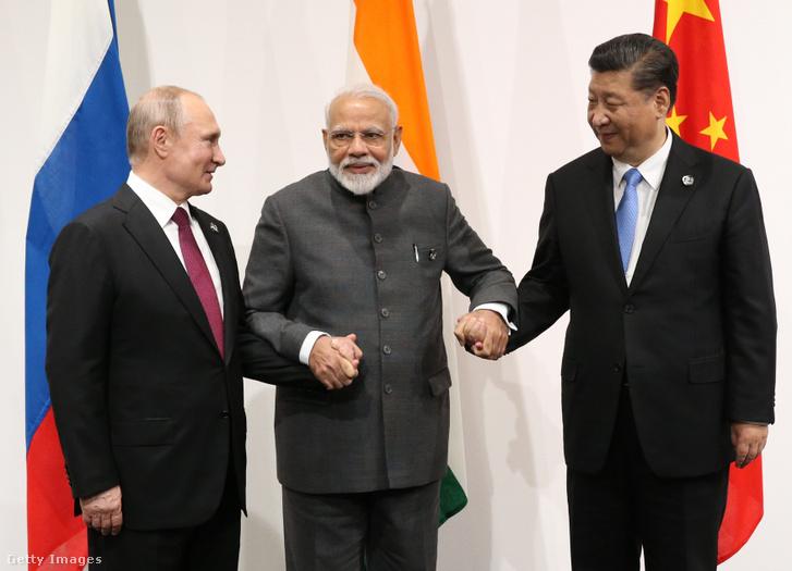 Narenda Modi (középen) indiai miniszterelnök és Hszi Csin-ping (jobbra) kínai pártfőtitkár-államfő a G20 oszakai találkozján Vlagyimir Putyinnal közös képen 2019. június 28-án