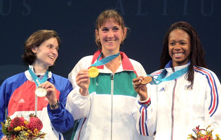Az olimpiai bajnok magyar Nagy Tímea boldogan mutatja aranyérmét a dobogón a második helyezett svájci Gianna Hablützel-Bürki (b) és a bronzérmes francia Laura Flessel-Colovic (j) között a sydneyi nyári olimpiai játékok női egyéni párbajtőr versenyének eredményhirdetésén 2000. szeptember 17-én.
