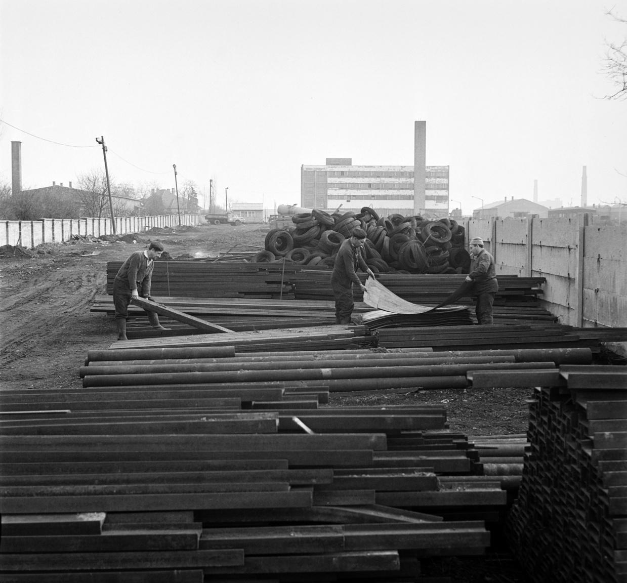 Rakodók vasidomokat, vaslemezeket pakolnak. A MÉH vállalatok által begyűjtött ócskavasnak közel 40 százaléka laza lemez volt, aminek mintegy harmadát bálázták. Laza állapotban legfeljebb 7 tonna fért belőle egy vasúti vagonba, bálázva a háromszorosa. A bálázott lemeznek az az előnye is megvolt, hogy azonnal beolvaszthatták, vagyis a bálázóhelyről közvetlenül szállíthatatták Dunaújvárosba, Ózdra, Csepelre.