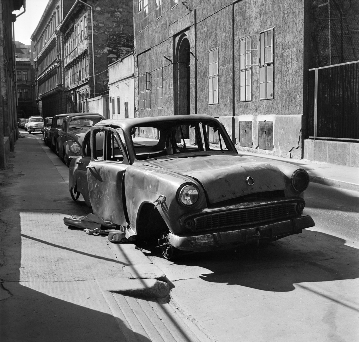 Egy Moszkvics 407-es rohad a budapesti utcán az elszállítást várva. A Moszkvicsnak ez az 1958-ban bemutatott típusa nagy népszerűségnek örvendett az országban. Ekkoriban lehetett már magánembereknek is autót venni, mert addig leginkább csak az állami szervek, közületek, vállalatok, hivatalok, körzeti orvosok jutottak gépkocsihoz. Innentől kezdve a Moszkvics a leggyakoribb autóvá vált Magyarországon mind magánemberek, mind pedig a vállalatok, állami szervek köreiben. Szinte minden régi közelekedési témájú fotón fellelhető egy 407-es, hol rendőrkocsiként, hol taxiként, hol a TSZ elnök szolgálati kocsijaként.