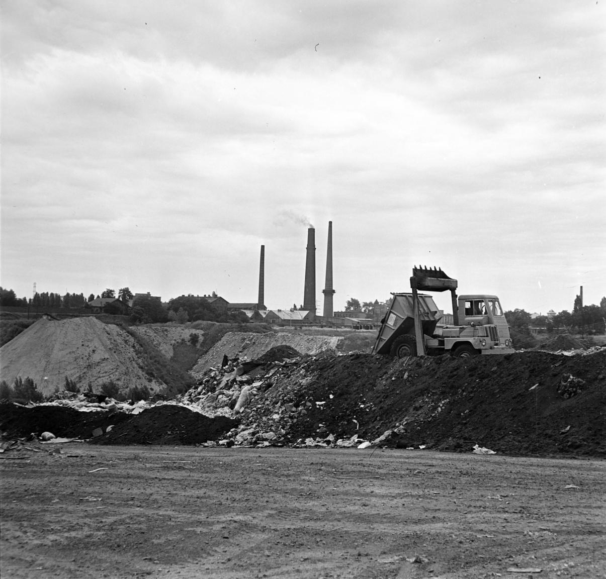 Dömper a szeméttelepen. Budapest egyik legnagyobb szemétlerakóhelye a hetvenes években Óbuda határában volt. Jól őrizték, táblák hívták fel a figyelmet arra, hogy a szemétbányába belépni és guberálni tilos. A beérkező teherautóknak jegyük volt, térmester írta alá a menetleveleket, pecsételte le az okmányokat. Bálint Nándor, az óbudai bánya térmestere arról mesélt egy korabeli újságcikkben, hogy a szemétszállító munkások a tilalmak ellenére külön zsákba szedték az értékesíthető hulladékot. A kukákból például napi 500—600 kiló kenyér összejött, amit a város szélén élő, disznókat tartó családok mind megvettek, kilóját két forintért. A bányák környékét ügynökök és maszek kisiparosok járták, hogy felvásárolják a kincset érő műanyagot, ledarálják, újraöntsék és meggazdagodjanak belőle. Volt példa arra hogy teherautónyi, jó állapotban levő hangszórót vittek a szemétdombra; de került a bányákba sok tucat rozsdás, leselejtezett gyermekkerékpár gyári csomagolásban. Ezeknek aztán valahogy mindig gazdájuk akadt.