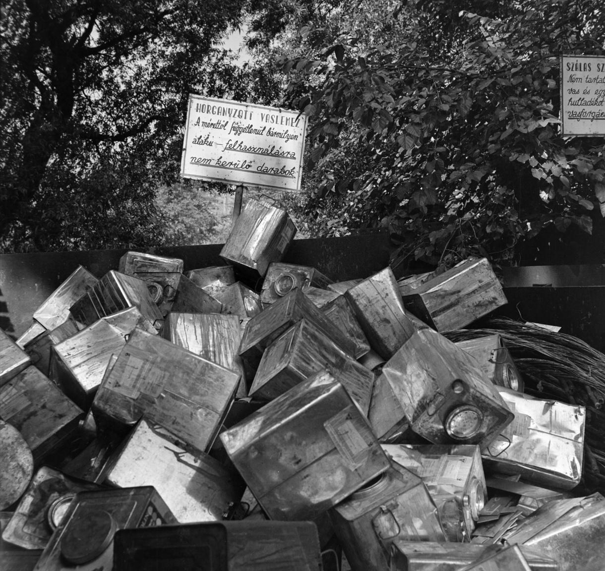 """""""Gyűjtsd a vasat és a fémet, ezzel is a békét véded!"""" - így szólt a jelszó a II. világháborút követő évtizedben Magyarországon. Az erőltetett iramban iparosodó, de nyersanyagban szegény országnak szüksége volt újrafeldolgozható fémre, papírra. A gyűjtés koordinálására hozták létre 1950-ben Melléktermék és Hulladék Egyesülést, a későbbi MÉH-et. A kereslet és kínálat azonban nehezen hangolódott össze. A képen horganyzott vaslamezek gyűjtésére szolgáló konténer, csurig tele használt fém festékdobozzal, miközben a festékgyárak arra panaszkodtak (1961, Figyelő), hogy """"a Kohó- és Gépipari Minisztériumhoz tartozó fémdoboz- gyártó vállalatok sem a mennyiségben, illetve választókban, sem pedig a csomagolóeszközök- minőségében nem tartanak lépést a festékipar ilyen irányú szükségletével. A 25 kg-os szögletes kannák és az 50 kg-os, festékhobokok esetében a festékipar krónikus problémákkal küzd""""."""