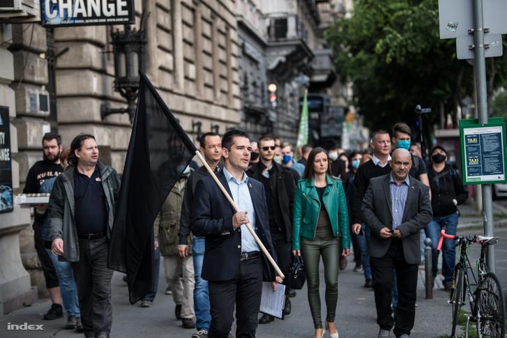 Novák Előd fekete zászlóval. Mellette Apáti István (b) és Dúró Dóra (j) az ORÖ székházához szervezett demonstráción