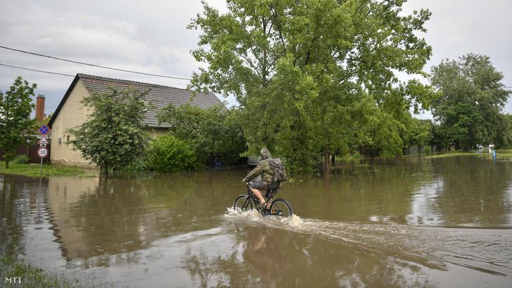 Egy férfi kerékpározik az esõvízzel elöntött Déli soron Debrecenben 2020. június 16-án.