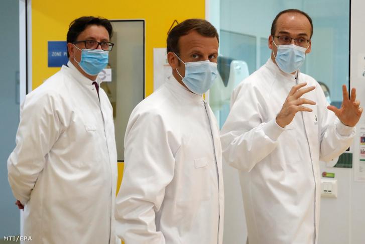 Emmanuel Macron francia elnök (k) Paul Hudson vezérigazgató (b) és Thomas Triomphe alelnök kíséretében látogatást tesz a koronavírus elleni oltóanyag-tesztelést folytató francia Sanofi gyógyszeripari vállalat laboratóriumában Marcy-l'Etoile-ban 2020. júnus 16-án.