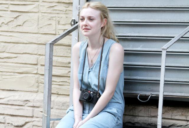 Dakota Fanning a filmforgatáson, fényképezővel a nyakában
