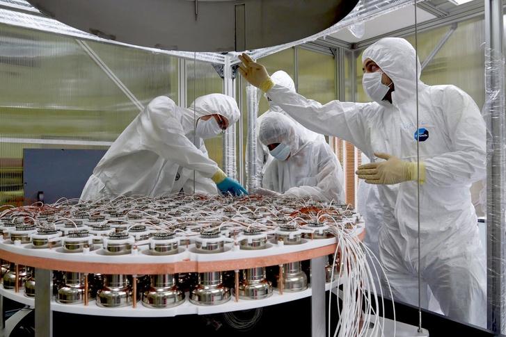 A detektorban működő fotoelektron-sokszorozókat szerelő kutatók