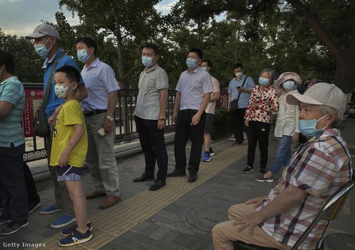 Tesztre várakoznak akik a Hszinfadi piacon jártak 2020. június 16-án.